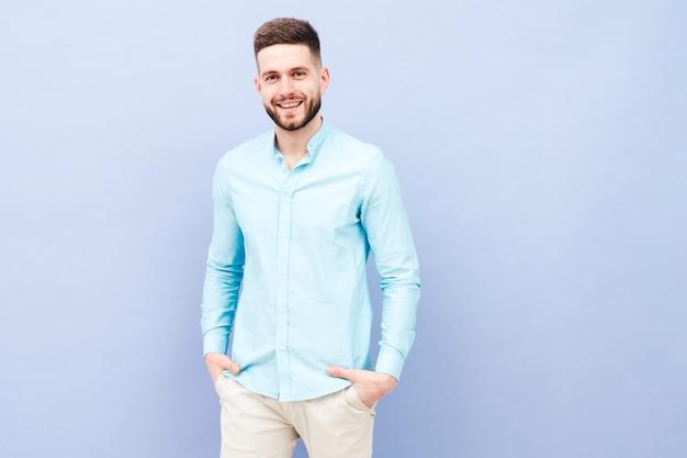 Retrato de guapo sonriente joven vistiendo pantalones y camisa casual