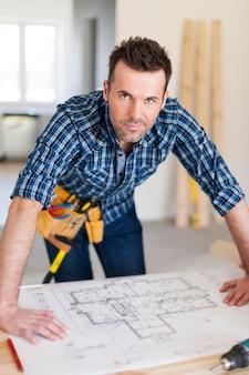 Retrato de guapo trabajador de la construcción con planos de viviendas
