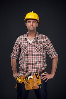 Retrato de guapo trabajador manual con cinturón de herramientas