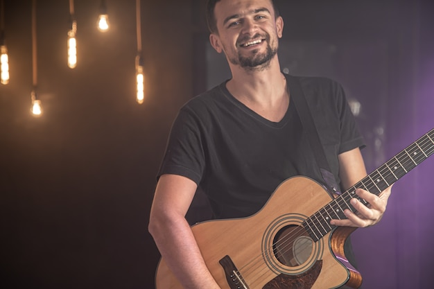Retrato de guitarrista sonriente en camiseta negra tocando la guitarra acústica.