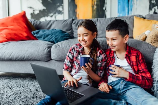 Retrato de hermano y hermana viendo una película divertida con una taza de jugo, mientras usa la computadora portátil.