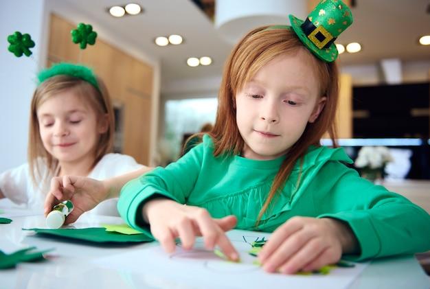 Retrato de hermanos haciendo adornos en la fiesta irlandesa