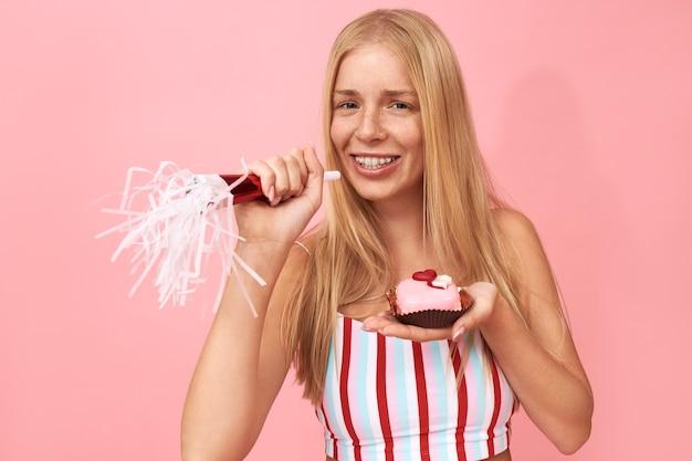 Retrato de hermosa adolescente con pecas y tirantes en los dientes disfrutando de la fiesta de cumpleaños