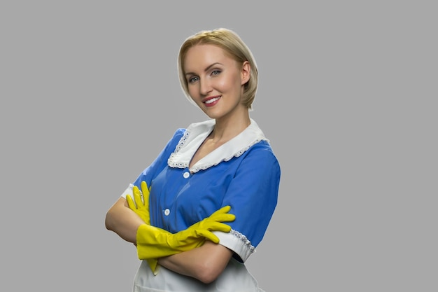 Retrato de hermosa ama de llaves cruzó sus brazos. joven camarera sonriente en uniforme ordenado y guantes contra un fondo gris. concepto de servicio de limpieza de la casa.
