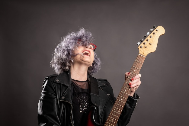 Retrato de hermosa anciana tocando la guitarra eléctrica