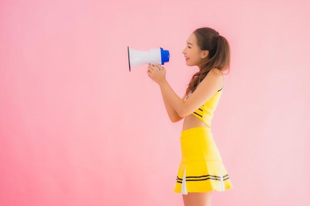 Retrato hermosa animadora joven asiática con megáfono
