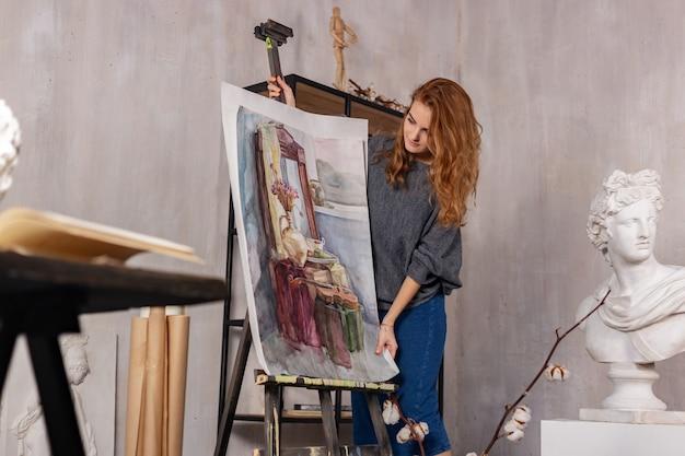 Retrato de una hermosa artista femenina que trabaja en un proyecto de arte en su estudio