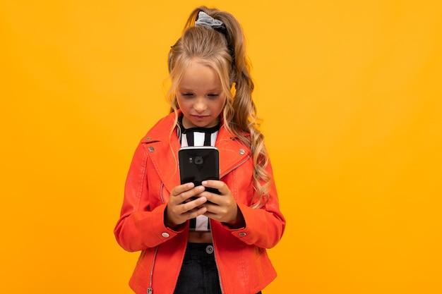 Retrato de hermosa chica caucásica con cabello largo y rubio y cara bonita en camiseta blanca y negra, chaqueta naranja y pantalón negro sostiene sonrisas de teléfono