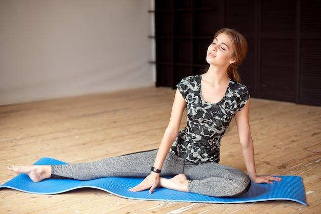Retrato de una hermosa chica deportiva en ropa deportiva descansando después de un entrenamiento físico de agua potable