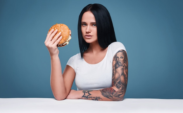 Retrato de hermosa chica encantadora tatuaje sosteniendo hamburguesa