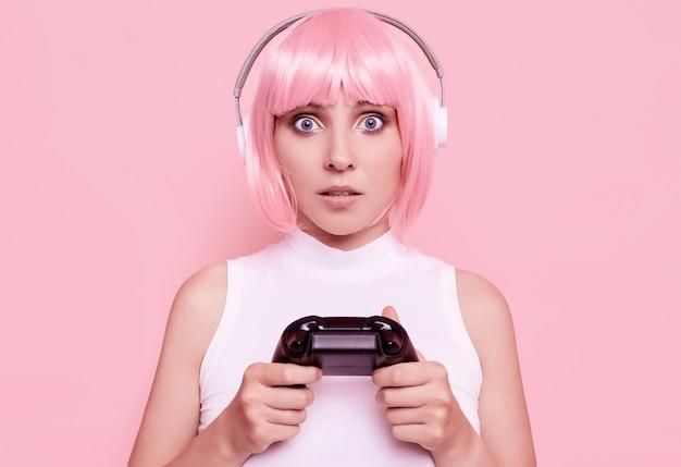 Retrato de hermosa chica gamer feliz con cabello rosado jugando videojuegos con joystick en colorido en estudio