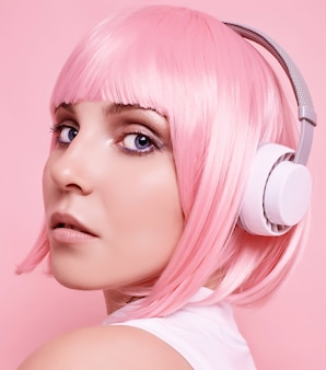 Retrato de hermosa chica hipster brillante con cabello rosado disfruta de la música en auriculares en colores