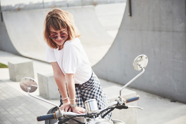 Retrato de una hermosa chica hipster sentada en un scooter retro negro, sonriendo posando y disfrutando del cálido sol primaveral.