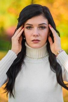 Retrato de una hermosa chica morena en un cálido día de otoño en el parque