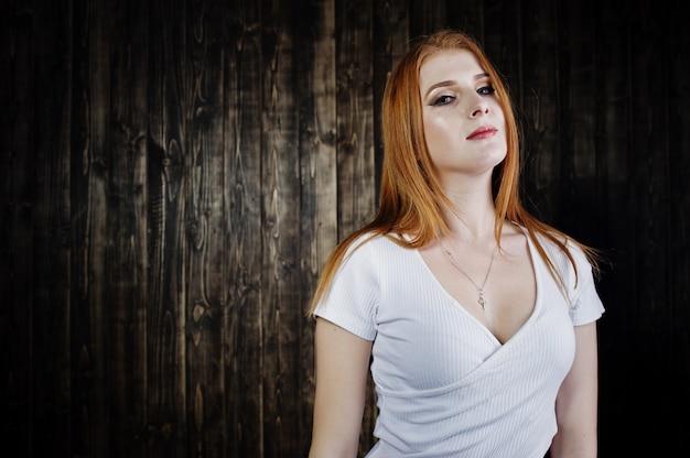 Retrato de una hermosa chica pelirroja en camiseta blanca y pantalones cortos de mezclilla posando en el estudio junto a la pared de madera.