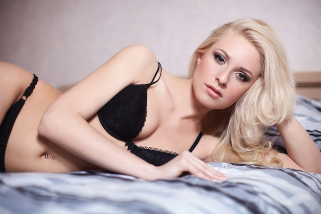 Retrato de hermosa chica rubia sexy acostada en la cama en lencería negra con maquillaje brillante y peinado