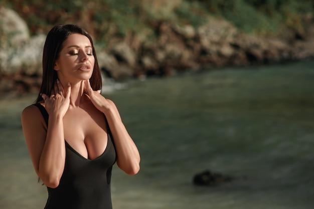 Retrato de una hermosa chica en traje de baño negro que toca su cuello en la playa. sesión de fotos sexy