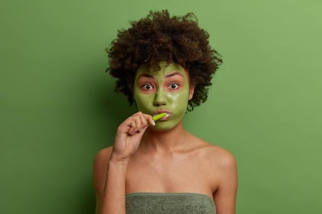Retrato de hermosa dama afroamericana encantadora tiene procedimientos de rutina matutinos, usa máscara facial anti-envejecimiento para rejuvenecimiento, cepilla los dientes, envuelto en una toalla de baño, aislado sobre una pared verde