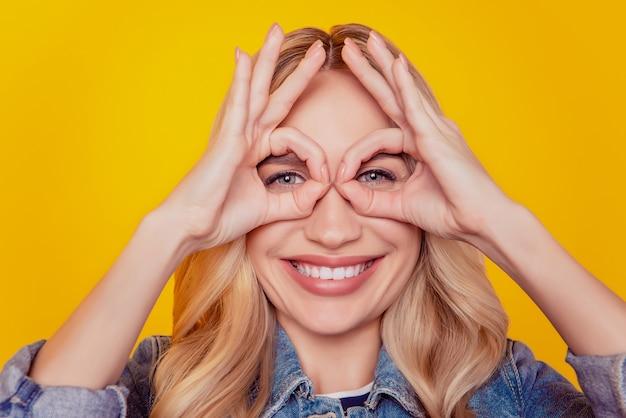Retrato de hermosa dama bonita linda mostrar signos okey cubrir ojos hacer binoculares ver sobre fondo amarillo