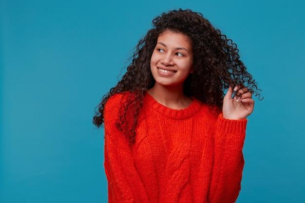 Retrato de hermosa dama con cabello oscuro y rizado en suéter de punto rojo sostiene un mechón de cabello en su mano, sonriendo