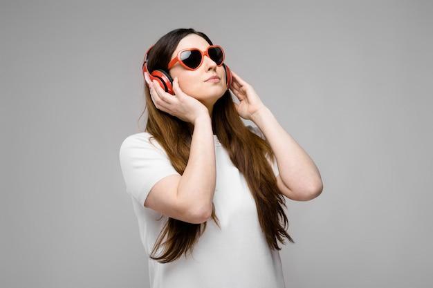 Retrato de hermosa emocional modelo plus size en auriculares y gafas de sol de pie mirando a otro lado
