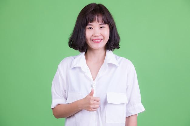 Retrato de hermosa empresaria asiática con pelo corto contra chroma key o pared verde
