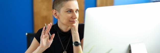 Retrato de hermosa empresaria hablando por videollamada. computadora moderna con símbolo. encantadora dama saludando. concepto en línea de tecnología y negocios