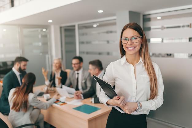 Retrato de hermosa empresaria en ropa formal, con largo cabello castaño y anteojos sosteniendo el portapapeles mientras está de pie en la sala de juntas.