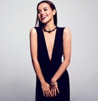 Retrato de hermosa empresaria sonriente en vestido negro con maquillaje de noche y labios rojos aislados en gris