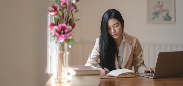 Retrato de hermosa empresaria trabajando en su nuevo proyecto mientras lee información de libros en una cómoda oficina