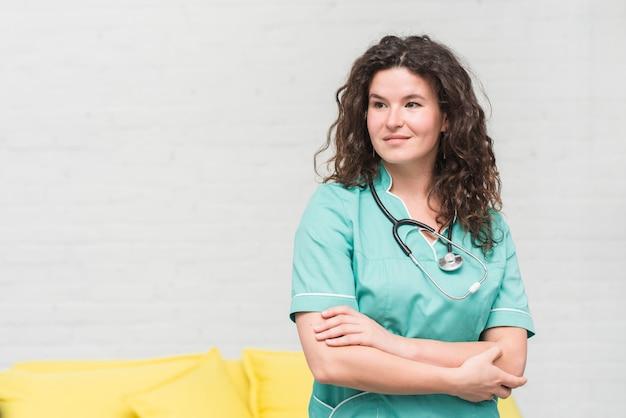 Retrato de hermosa enfermera femenina contra la pared blanca