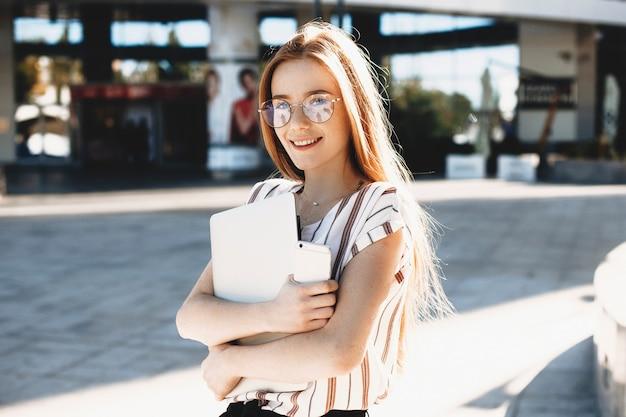 Retrato de una hermosa estudiante pelirroja con pecas mirando a la cámara sonriendo y sosteniendo un teléfono inteligente y una computadora portátil contra un edificio.