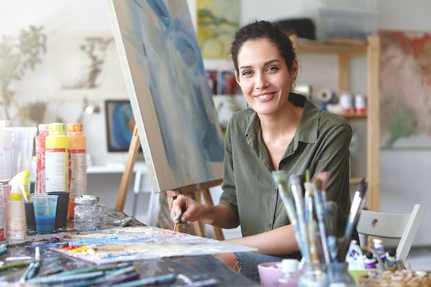Retrato de una hermosa y excitada joven artista femenina morena en una blusa informal de color caqui, mezclando pintura al óleo en la paleta con un cuchillo de pintura, apasionada por su ocupación y proceso de creación