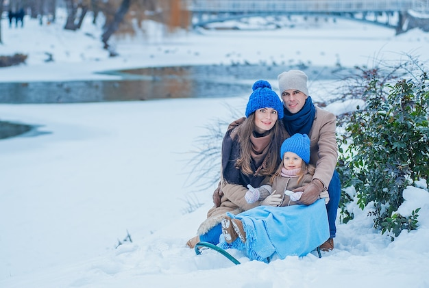 Retrato de una hermosa familia joven en ropa beige y azul en el fondo de un lago congelado en el parque