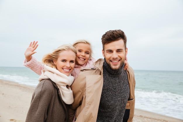 Retrato de una hermosa familia con una pequeña hija divirtiéndose