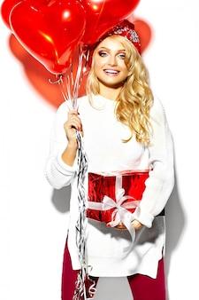 Retrato de hermosa feliz dulce mujer rubia sonriente niña sosteniendo en sus manos una gran caja de regalo de navidad y globos de corazón en ropa casual de invierno hipster rojo, en suéter blanco cálido