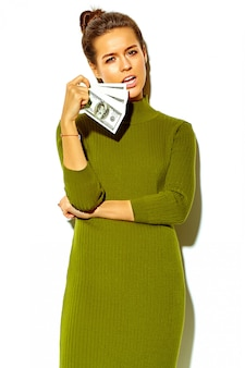 Retrato de hermosa feliz linda mujer morena sonriente niña en ropa de verano casual hipster verde aislado en blanco con billete de dólar en la boca