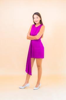 Retrato hermosa joven asiática en acción sobre fondo de color aislado