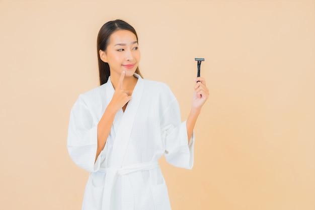 Retrato hermosa joven asiática con afeitado en beige
