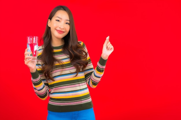 Retrato hermosa joven asiática con agua potable y píldora en la pared roja