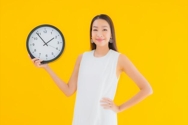 Retrato hermosa joven asiática con alarma o reloj