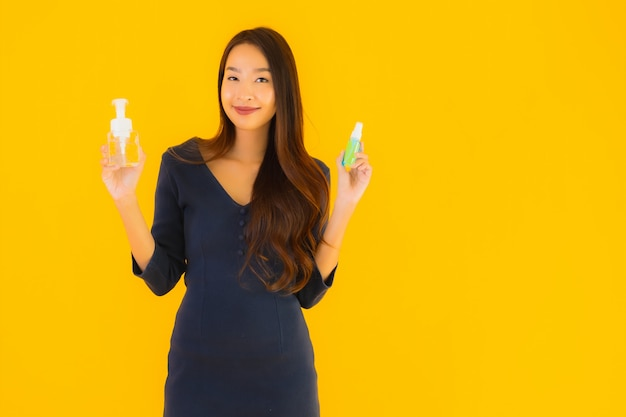 Retrato hermosa joven asiática con alcohol en gel y spray