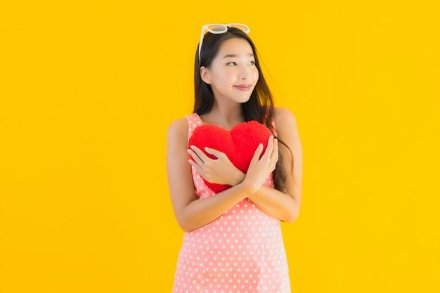 Retrato hermosa joven asiática con almohada de corazón