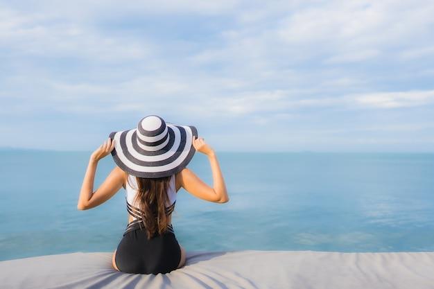 Retrato hermosa joven asiática alrededor del mar playa océano