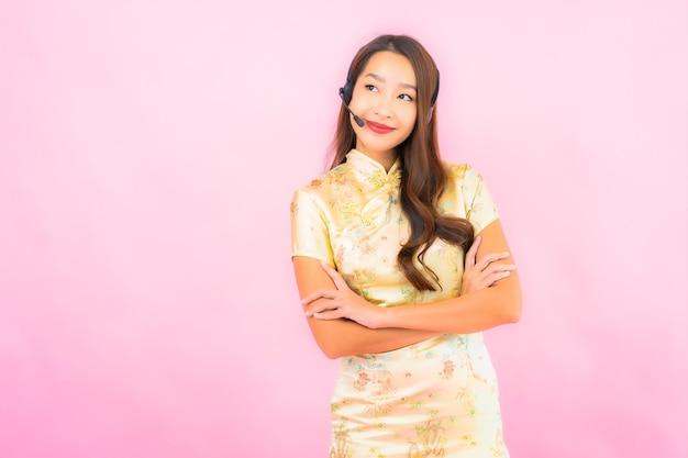 Retrato hermosa joven asiática atención del centro de llamadas del cliente en la pared de color rosa