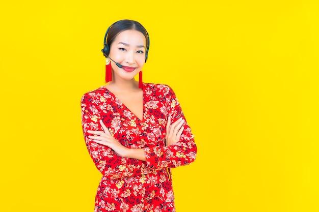 Retrato hermosa joven asiática con auriculares para atención de centro de llamadas al cliente en pared amarilla