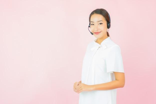 Retrato hermosa joven asiática con auriculares para cliente de centro de llamadas en pared rosa