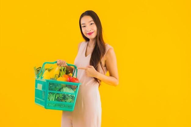 Retrato hermosa joven asiática con bolsa de compras de la cesta de la compra