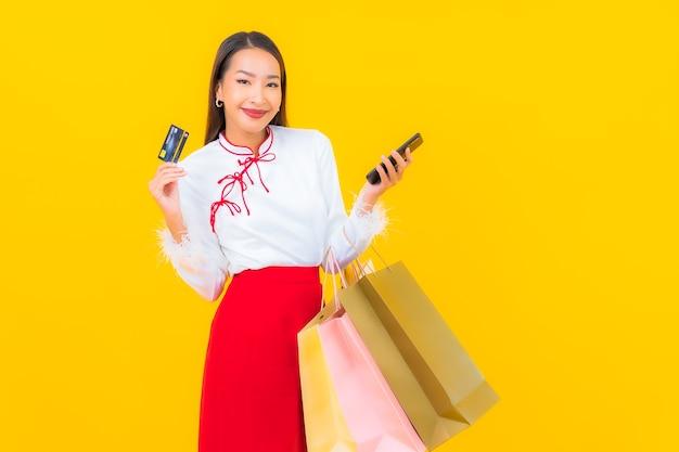 Retrato hermosa joven asiática con bolsa de compras y tarjeta de crédito en amarillo