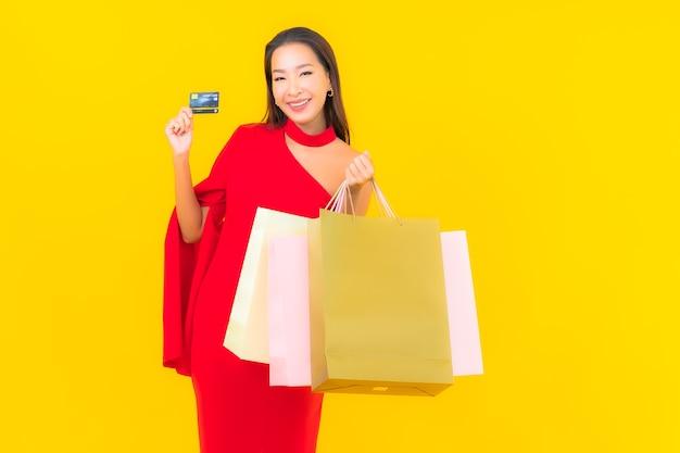 Retrato hermosa joven asiática con bolsa de compras y tarjeta de crédito